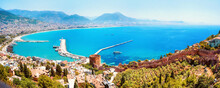 Beautiful Panoramic Image Of Bay Of Resort Town Of Alanya With Symbol Of City - Red Tower, Ancient Fortress Walls, Turquoise Sea, Chain Of Mountains On Horizon.