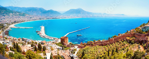 Fotografie, Tablou Beautiful panoramic image of bay of resort town of Alanya with symbol of city - Red Tower, ancient fortress walls, turquoise sea, chain of mountains on horizon