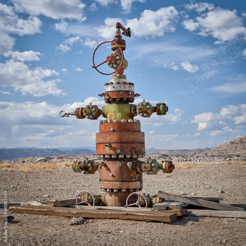 Carta da parati unused head of oil well with numerous valves in a desert landscape of central Ut