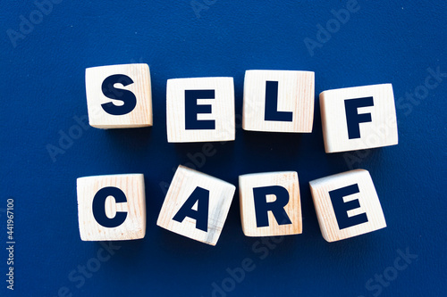 Photo SELF CARE - text on wooden cubes on a blue background
