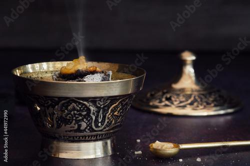 Fototapeta Fragrant frankincense resin (olibanum) on glowing charcoal in a censer