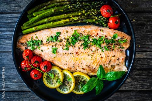 Obraz na plátně Roasted trout fillet with asparagus and vegetables served on black plate on wood