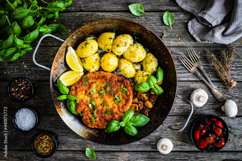 Slika na platnu Breaded fried pork chop, potatoes and white mushrooms on wooden table