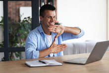 Happy Smiling Deaf Young Caucasian Man Uses Sign Language While Video Call Using Laptop While Sitting At Home, Virtual Communication Concept