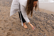 Woman With Stones At Seaside