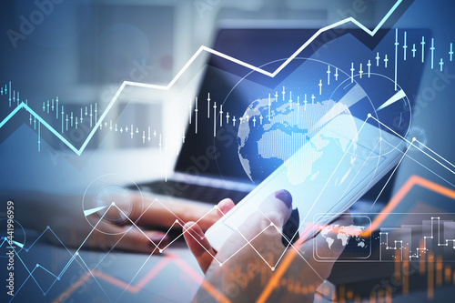 Businesswoman or stock trader analyzing stock graph chart using smartphone with Fototapete