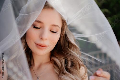 beautiful bride with long wavy hair under the veil Fotobehang