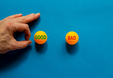 Good Or Bad Symbol. Male Hand Is About To Flick The Ball. Orange Table Tennis Balls With Words Good Bad. Beautiful Blue Background. Business, Good Or Bad Concept.