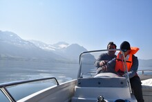 Father Teaching His Son How To Drive A Motorboat On Lake Lucerne. The Son Is Wearing Orange Life Jacket. There Is A Lot Of Copy Space On The Background.