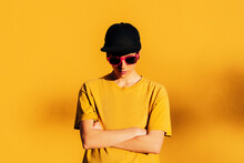 Cool Informal Woman With Crossed Arms Near Yellow Wall