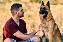 Man Sitting On Meadow With Fluffy Dog