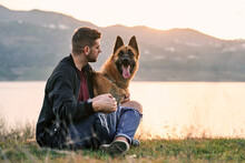 Smiling Man With Dog On Shore Of Lake