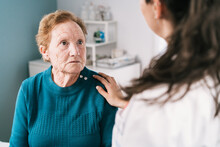 Crop Physician Supporting Sad Senior Patient During Consultation In Clinic