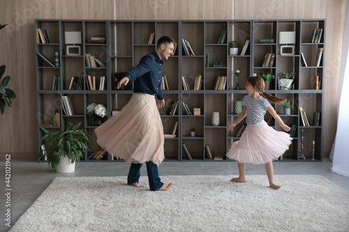 Fotografia Loving happy young Caucasian father wear pink princess skirt play dance with teenage daughter at home