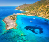 Fototapeta Kawa jest smaczna - Aerial view of beautiful yachts and boats on the sea at sunset in summer. Akvaryum koyu in Turkey. Top view of luxury yachts, sailboats, clear blue water, rock, sky, mountain and green trees. Travel