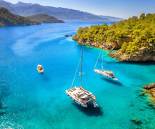 Aerial View Of Beautiful Yachts And Boats On The Sea At Sunset In Summer In Turkey. Top View Of Luxury Yachts, Sailboats, Clear Blue Water, Rock, Sky, Mountain And Green Trees. Travel. Landscape