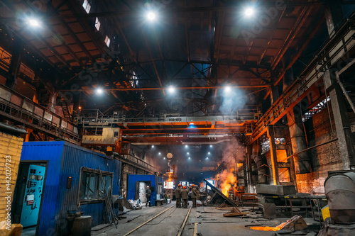 Fotografie, Obraz Steel production at metallurgical plant, large workshop with beam cranes and underground blast furnace