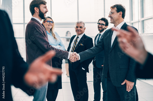 Fotografia confident business people shaking hands with each other.