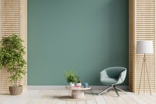 Green Armchair And A Wooden Table In Living Room Interior With Plant,dark Green Wall.