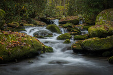 Low Angle Of Water Rushing Around Mossy Boulders