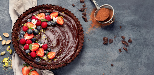 Delicious chocolate tart on gray background. Homemade desserts concept.