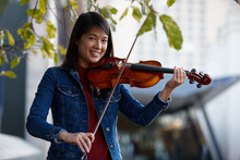 Young Asian Female Violin Player Practising Outdoors