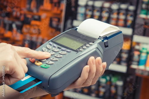 Fototapeta Payment terminal with credit card as device using for cashless paying for shopping in shop