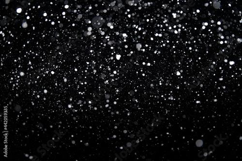Cuadros en Lienzo Many snowflakes in blur on black background