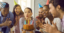 Young People Having Fun And Celebrating Friend's Birthday. Banner With Group Of Multiethnic Friends Applaud As Birthday Girl In Her 20s Twenties Makes Funny Face And Blows Candles Lit On Party Cake