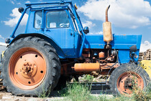 Old Dilapidated Blue Wheeled Tractor In The Back Yard