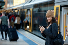 Commuter Coming Off Train At Station Using Mobile Phone