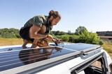 Fototapeta Miasto - Man connecting solar panels on top of a camper van