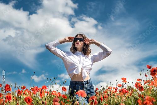Canvastavla brunette girl in white blouse walking along a poppy field