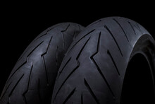 Closeup Image Of Set Of New Racing Road Motorcycle Tyres Against Black Background.