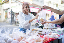 A Beautiful Girl In A Veil Buys Takjil Food In A Plastic Bag From A Roadside Stall Seller