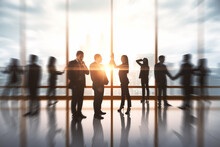 Successful Businessmen Hi-fiving In Blurry Office Interior With Sunlight. Success And Work Ethics Concept.