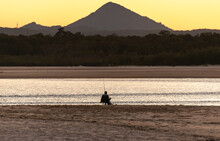 Rear View Of Fisherman Sitting On The Beach At Sunset Whit Mountain And Sea Landscape