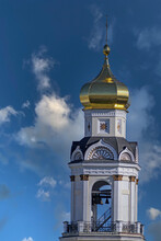 The Belfry Of An Orthodox Church On The Background Of A Blue Sky With White Clouds