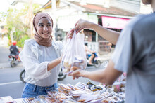 A Beautiful Girl In A Headscarf Takes A Takjil Food Order With A Plastic Bag From A Roadside Stall Seller
