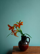 Tiger Lily In Ceramic Vase With Shadow Turquoise Wall Background. Lilium Lancifolium Orange Flowers Bouquet On Wooden Farmhouse Table. Summer Cottagecore Aesthetic Country Rural Minimalism Dark Style.