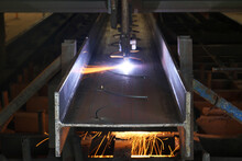 Section Of Steel Structure In Drilling Process With Sparks Fly From Drill Machine Uses For Construction Industry.