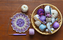 Crochet A Delicate Round Striped Lace Doily. Balls Of Cotton Yarn For Hand Knitting In A Wicker Basket On Wooden Table. Needlework And DIY Concept. Flat Lay, Copy Space, Top View, Close-up, Mock Up