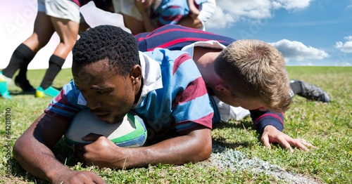 Composition of male rugby team playing and holding rugby ball at stadium