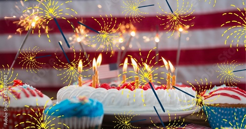 Composition of lit sparkler with cake and candles and american flags