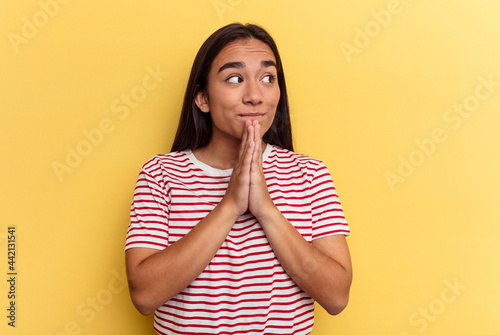 Foto Young mixed race woman isolated on yellow background praying, showing devotion, religious person looking for divine inspiration