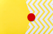 Solid And Patterned Yellow And White Paper Background With A Hand Painted Red Wooden Disc