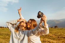 Cheerful Woman Taking Selfie With Vintage Camera