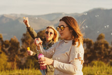 Happy Women With Soap Bubbles In Nature