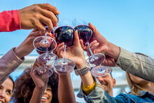Low Angle Cropped View Of A Diverse Group Of Friends In A Party Making A Celebratory Toast Clinking Wine Glasses. Happy People Having Fun At Summer Sunset Happy Hour. Focus On Glasses From Below.