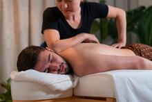 Masseuse Massaging Back Of Male Client